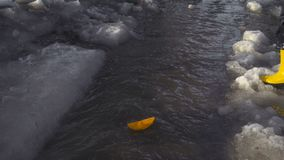 Little boy launches a paper boat at the spring creek stock video