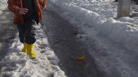 Little boy launches a paper boat at the spring creek. Little boy in yellow rainboots launches a paper boat at the spring creek of melting ice, slow motion stock video footage