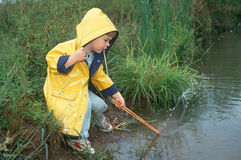 Little boy in yellow raincoat by stream Royalty Free Stock Photos