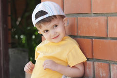 Little boy in yellow shirt at brick wall Stock Photography