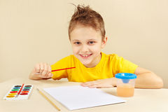 Little boy in yellow shirt going to paint colors Royalty Free Stock Images