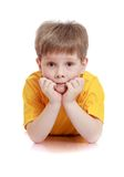 Little boy in a yellow t-shirt lying on the floor Royalty Free Stock Photo