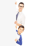 Little boy and a young adult standing behind blank panel Stock Photos