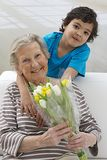 Little boying offering flower to his grandmother Stock Image