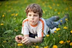 Little boyl lying in grass Stock Photos