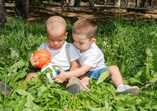 Little boys: African American and caucasian  with soccer ball in park on nature at summer. Royalty Free Stock Image