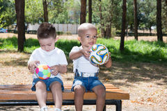 Little boys: African American and caucasian  with soccer ball in park on nature at summer Stock Photography