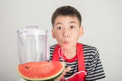 Little boys blend water melone juice by using blender home royalty free stock image