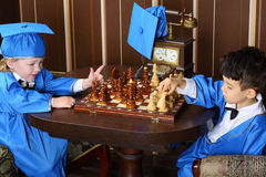 Little boys in blue suits play chess Stock Photo
