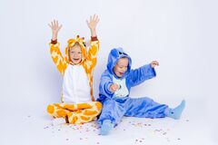 Little boys brothers in fun bright costumes indulge and have fun on a white isolated background with confetti, children`s birthda