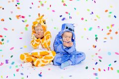 Little boys brothers in fun bright costumes sit on a white isolated background and blow away confetti, children`s birthday, place