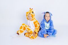 Little boys brothers in fun bright costumes sit on a white isolated background, children`s birthday, place for text