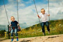 Little boys brothers having fun on a swing outdoor Stock Images