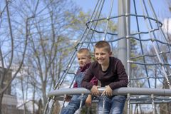 Little boys in cap climb on jungle gym at park royalty free stock photo