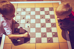 Little boys children playing checkers outdoor Stock Image