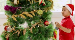 Little boys decorating the christmas tree stock footage