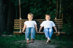 Little boys dreaming on swing Stock Image