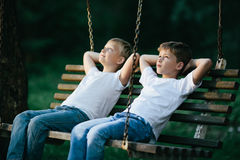 Little boys dreaming on swing. Photo of two little boys dreaming on swing Royalty Free Stock Photography