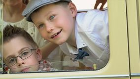 Little boys drive the standing retro car play about on the camera. Boys in a retro to clothes sit in the beautiful beige. On this video you can see as the large stock video