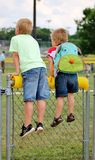 Little boys on a fence looking onto a baseball field Royalty Free Stock Images