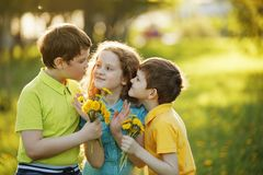 Little boys give his girl friend bouqet of yellow dandelions, sp royalty free stock photo