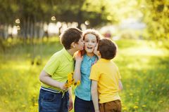 Little boys give his girl friend bouqet of yellow dandelions. royalty free stock photo