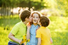Little boys give his girl friend bouqet of yellow dandelions, Royalty Free Stock Photos