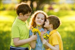 Little boys give his girl friend bouqet of yellow dandelions. stock images