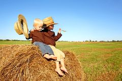 Little Boys Out in the Country on a Hay Bale. Two happy young children, a boy and his baby brother, are sitting on a hay bale in a field on a farm, wearing straw Royalty Free Stock Photos