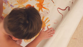 Little boys painting with their palms on paper Stock Photo