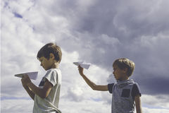 Little boys with paper planes against blue sky Stock Photos