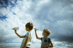 Little boys with paper planes against blue sky Stock Image