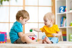 Little boys play together with educational toys. Two children boys play together educational toys in playroom Stock Photo