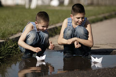 Little boys playing with paper boats in puddle Royalty Free Stock Image