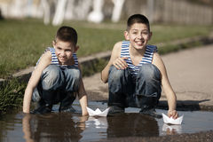 Little boys playing with paper boats in puddle Royalty Free Stock Images