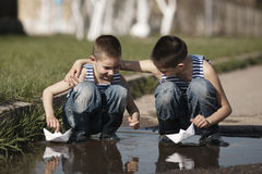 Little boys playing with paper boats in puddle Stock Images