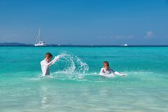 Little boys playing, splashing and spraying in sea waves. Kids having extreme splashing fun in sea water. stock images