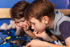 Little boys playing on tablet Stock Images