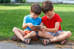 Little boys playing on tablet Stock Photo