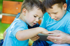 Little boys playing on tablet Stock Photos