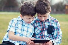 Little boys playing on tablet in nature Royalty Free Stock Image