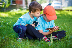 Little boys playing on wireless tools. At outdoor, smartphone and tablet stock photo