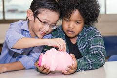 Little boys putting money into piggy bank. For future savings Royalty Free Stock Images
