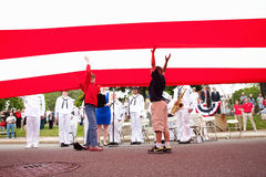 Little boys reach underneath US Flag Stock Photo