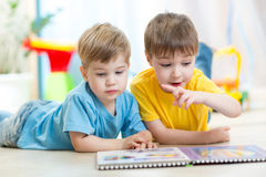 Little boys read together in nursery. Two little boys read together in nursery Royalty Free Stock Photo