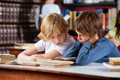 Little Boys Reading Book Together In Library. Little boys reading book together while sitting at table in library with classmates in background Stock Image