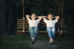 Little boys riding on a swing Royalty Free Stock Image