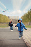 Little boys, running with kite stock images