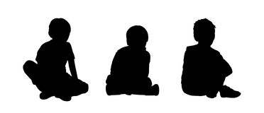 Little boys seated silhouettes set 2. Black silhouettes of three little boys age 5-10 seated on the floor face to the onlooker in different postures Stock Image