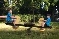 Little boys on seesaw. Happy little boys on seesaw in park Stock Photo